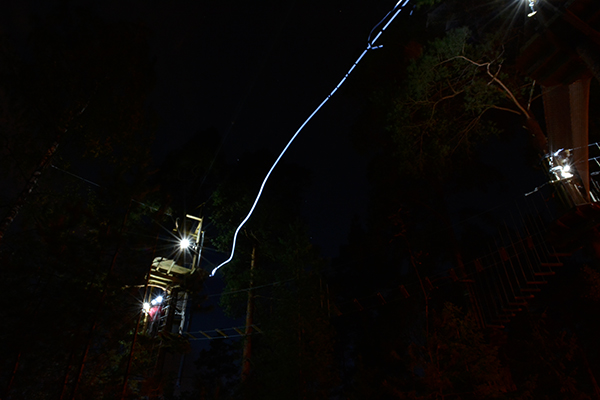 Tarzan swing at Treetop Adventure Huippu in the dark, lightpath of a headlamp in the air.
