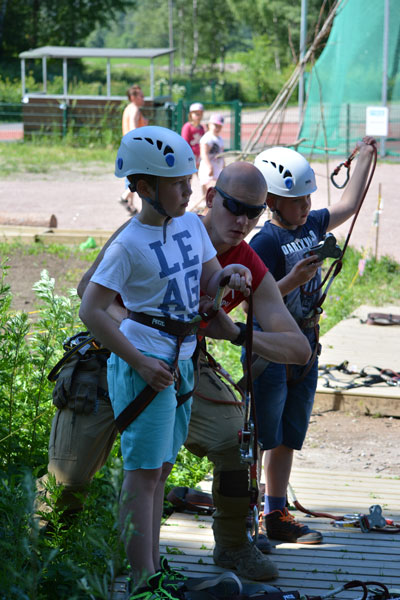 The instructors assist the adventurers to ensure that the harness fits properly.