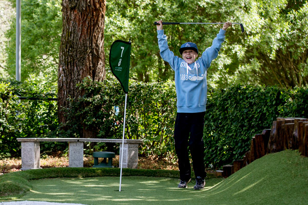 Adventure golf and the joy of succeeding. A boy jumps happily after a successful stroke.